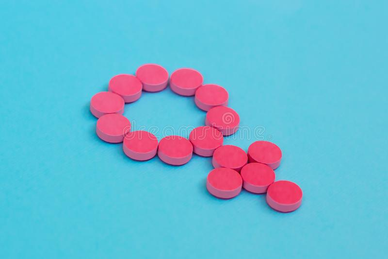 Preventiv- piller som genussymbol på blå bakgrund Kvinnlig hormonterapi arkivbilder