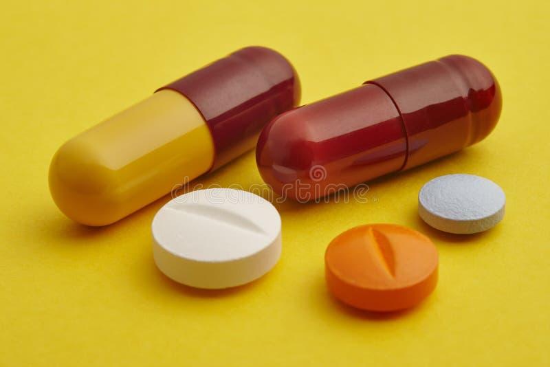 Preventivpillerar över en gul bakgrund Medikamentbehandling Vård- bil royaltyfri foto