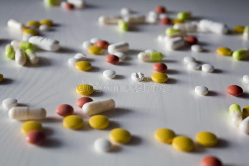 Preventivpillerar av olik färg på en vit wood tabell arkivbild