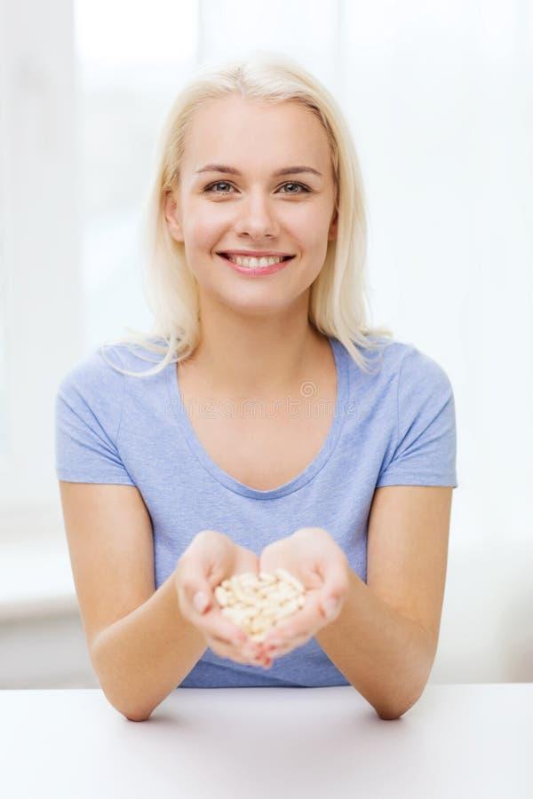 Preventivpillerar eller kapslar för lycklig kvinna hemmastadda hållande royaltyfria foton