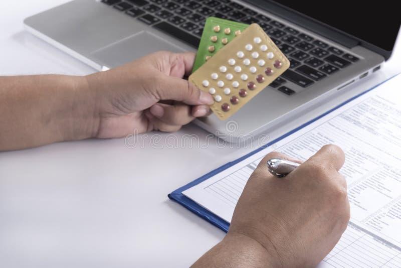 Preventivpillerar för födelsekontroll för doktorshand hållande arkivfoto