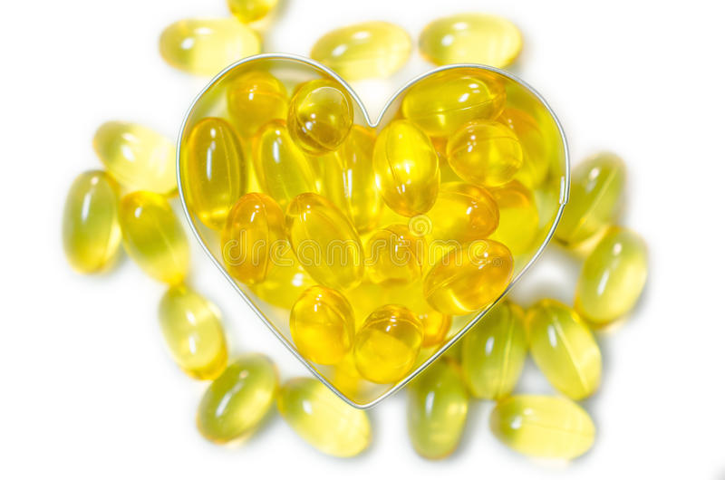 Preventivpillerar för fiskolja på hjärtaform boxas på isolerad vit bakgrund arkivbild