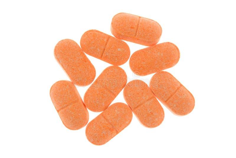 Preventivpillerar för vitamin C på vit arkivfoto