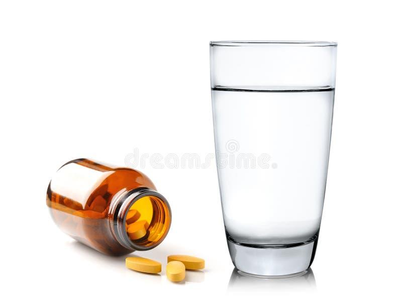 Preventivpillerar från flaskan och exponeringsglas av vatten på vit backgroun arkivfoton