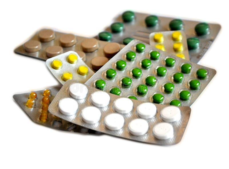 Preventivpillerar i bakgrund för vit för gräsplan- och gulingblåsapackar royaltyfri foto