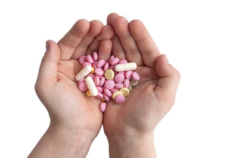 Preventivpillerar i barnets händer royaltyfri fotografi