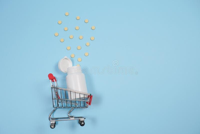 Preventivpillerar i shoppingvagn på blå bakgrund Begreppet: handel i mediciner, apotek arkivbild
