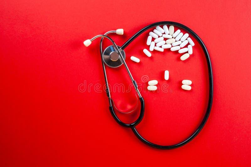 Preventivpillerar, minnestavlor och stetoskop på vit bakgrund fotografering för bildbyråer