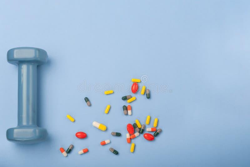 Preventivpillerar och liten hantelcloseup på blå bakgrund begrepp för medicinsportfarmakologi arkivfoton