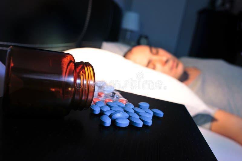 Preventivpillerar och ung man i säng royaltyfri bild