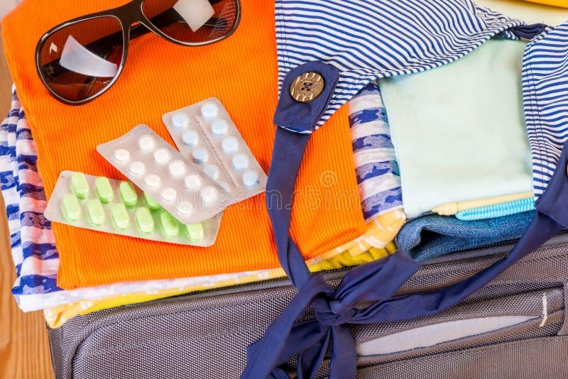 Preventivpillerar som behöver tas på en turlögn i en resväska nära intelligens arkivbild