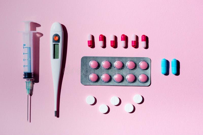 Preventivpillerar, termometer och injektionsspruta arkivfoton