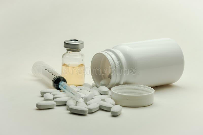 Preventivpillerar, vitaminer och injektionsspruta för injektion med läkarbehandlingar som isoleras på vit bakgrund royaltyfri foto