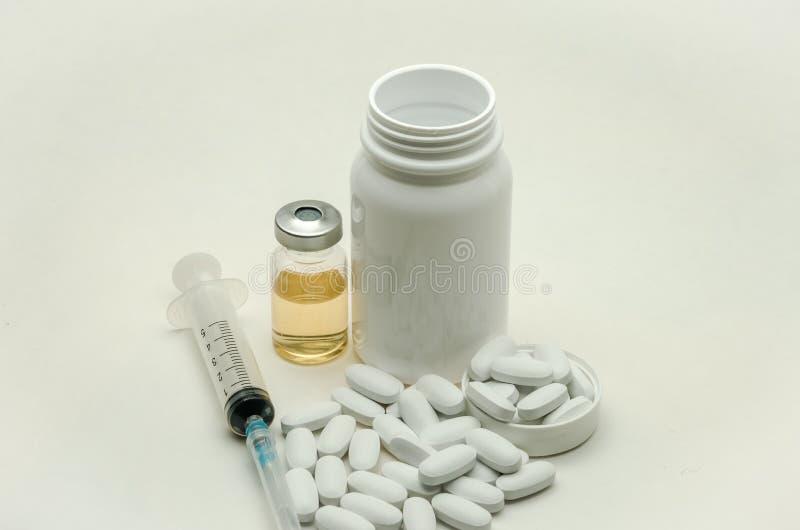 Preventivpillerar, vitaminer och injektionsspruta för injektion med läkarbehandlingar som isoleras på vit bakgrund royaltyfri fotografi