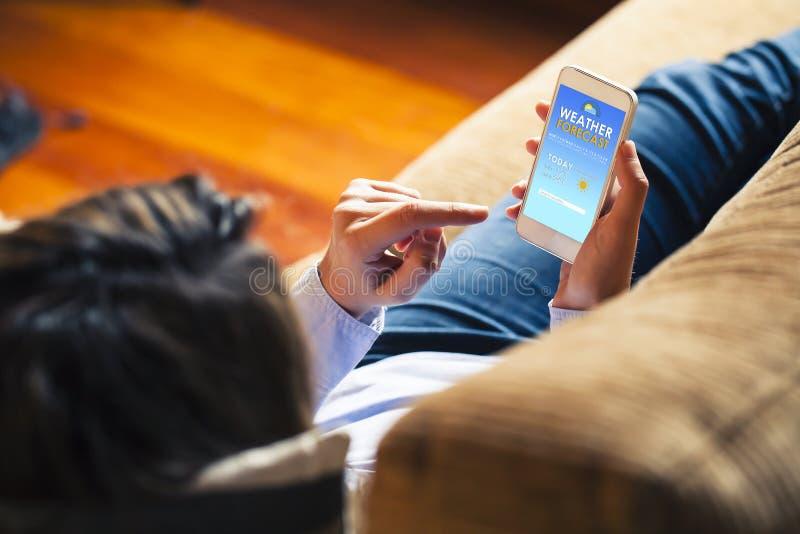 Previsão de tempo de consulta da mulher em um telefone celular em casa fotos de stock royalty free