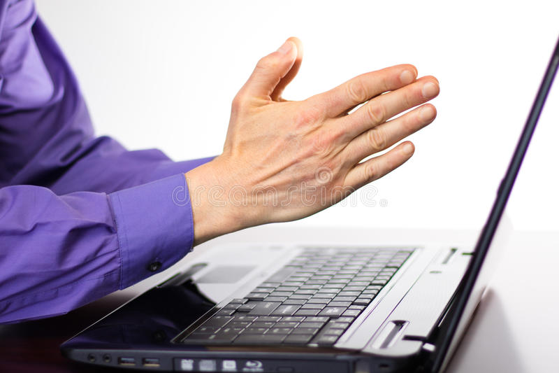 Preying Hands in front of Laptop Computer Display Screen. Image showing the side view of a laptop on a desk and someones hands pressed together in front of the royalty free stock image