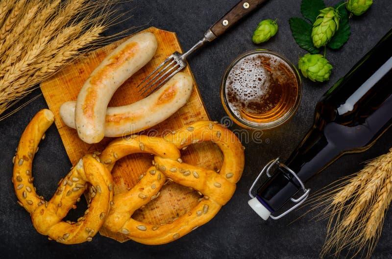 Prezel avec les saucisses grillées et la bière en verre photographie stock libre de droits