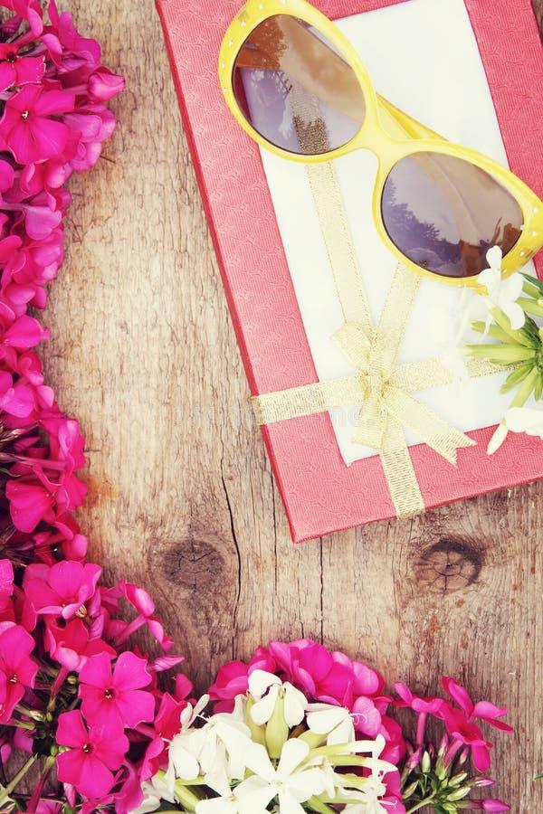 Prezentów okulary przeciwsłoneczni z jaskrawym czerwonym floksem i pudełko kwitniemy fotografia stock