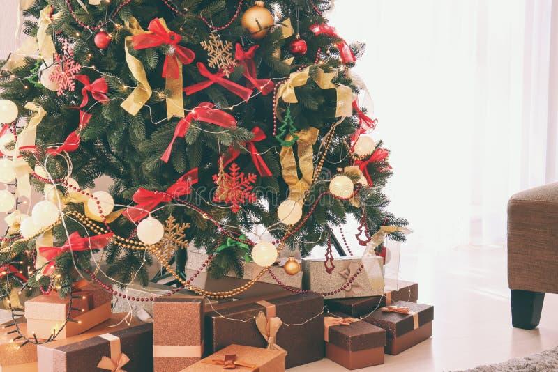 Prezentów pudełka pod pięknym Bożenarodzeniowym jedlinowym drzewem indoors zdjęcia royalty free