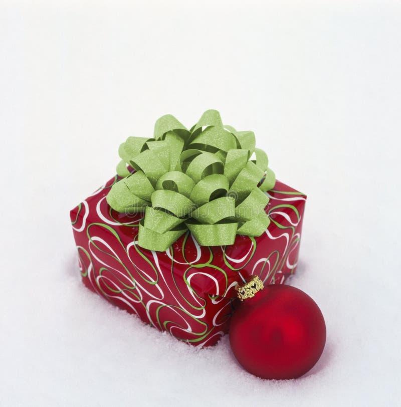 Prezent świąteczny z czerwonym i zielonym papierem do owijania, ozdobnym ozdobnym na białym tle śniegowym zdjęcie stock