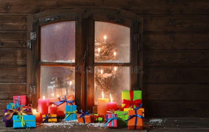 Prezent świeczki przy okno na bożych narodzeniach i pudełka zdjęcie royalty free