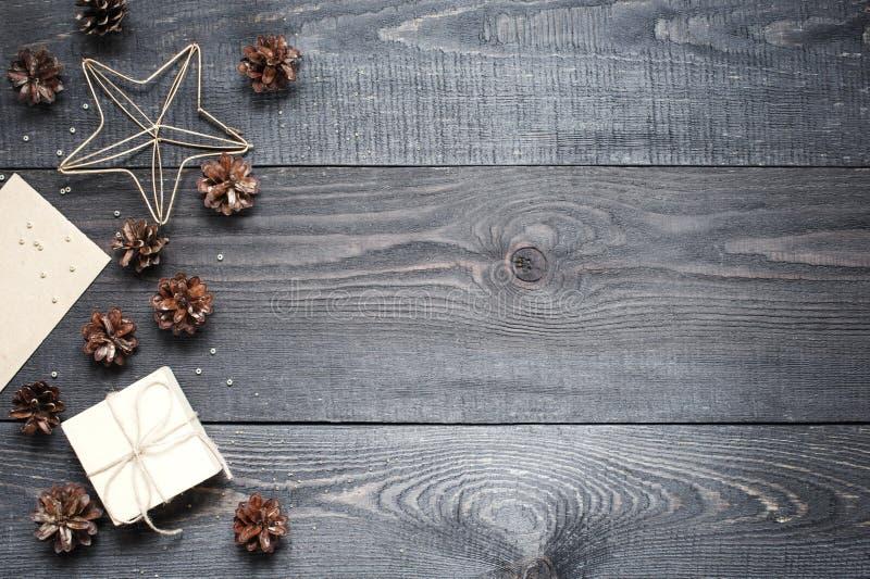 Prezent, karta, sosna rożki i cinnamonin na ciemnej drewnianej teksturze, obraz royalty free