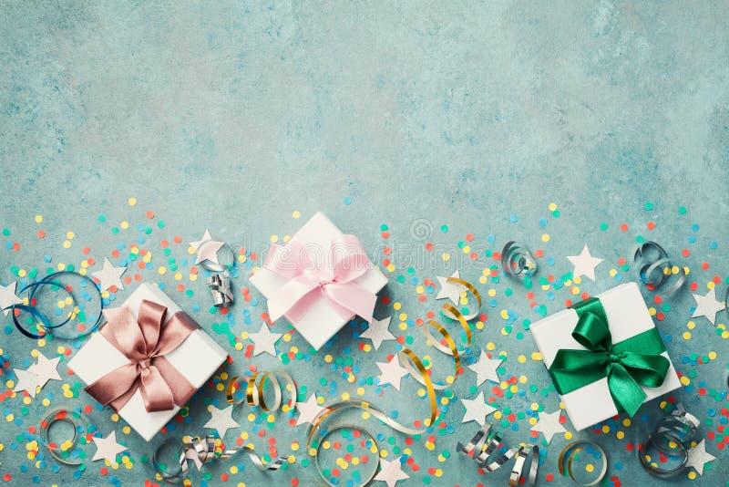 Prezent lub teraźniejszości pudełko dekorowaliśmy kolorowych confetti, gwiazdę i streamer na błękitnego rocznika stołowym odgórny obrazy stock