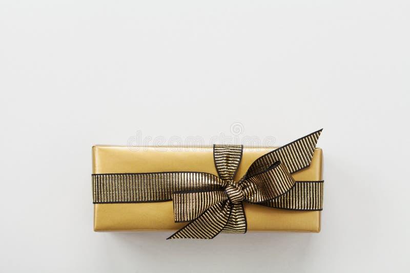 Prezent lub teraźniejszości pudełko dekorowaliśmy złocistego faborek na stołowym odgórnym widoku Mieszkanie nieatutowy skład dla  obraz royalty free