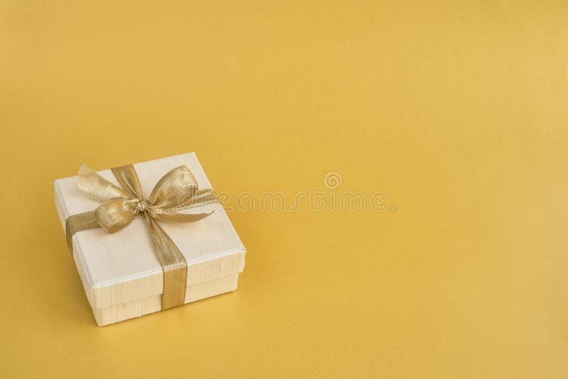 Prezent lub teraźniejszości pudełko dekorowaliśmy z złotym faborkiem na żółtym backg zdjęcia royalty free