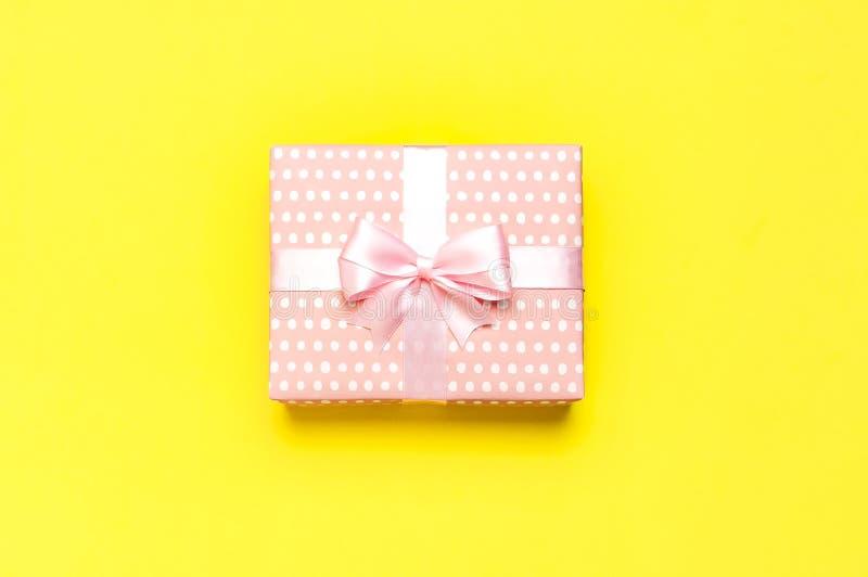 Prezent lub teraźniejszości pudełko z pięknym świątecznym faborkiem na żółtego tła odgórnym widoku Mieszkanie nieatutowy skład dl zdjęcia royalty free
