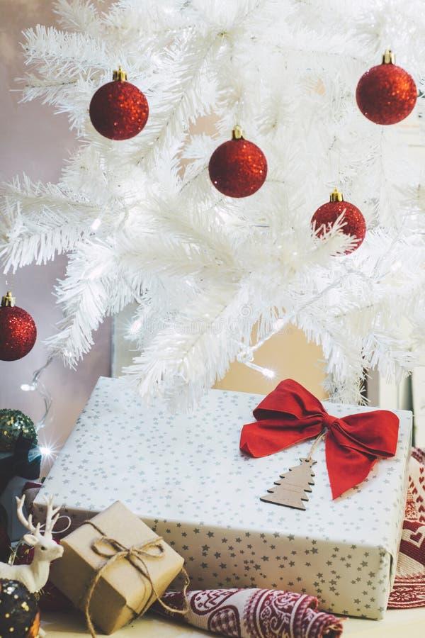 Prezent z czerwonym łękiem obok białego bożego narodzenia drzewa, strzał ornamenty obraz stock