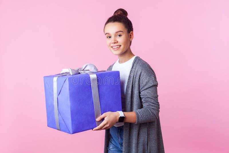 Prezent za wakacje i premie Portret wesołej nastolatki brunetki trzymającej pudełko na prezent i uśmiechającej się różowe tło obraz stock