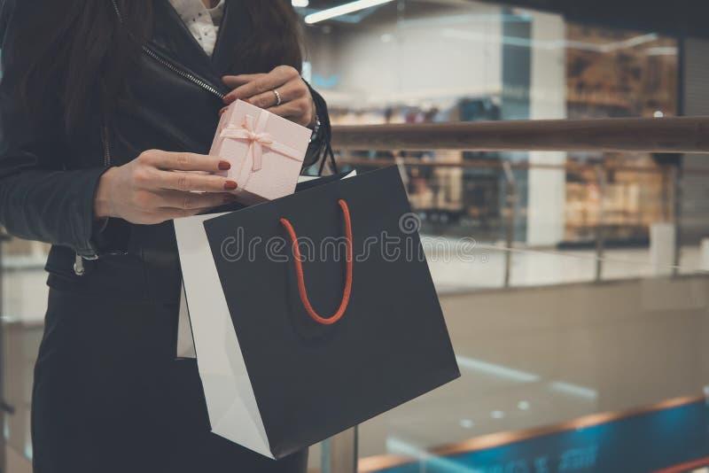 prezent zdojest w rękach dziewczyna na tle, centrum handlowe zakupy, prezenty, sprzedaż, nowego roku zakupy Kobieta stawia a zdjęcie royalty free