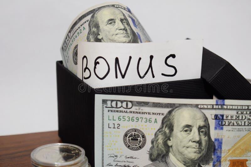 Prezenta pakunek z dolarami na stole na białym tle wpisowa premia zdjęcia royalty free