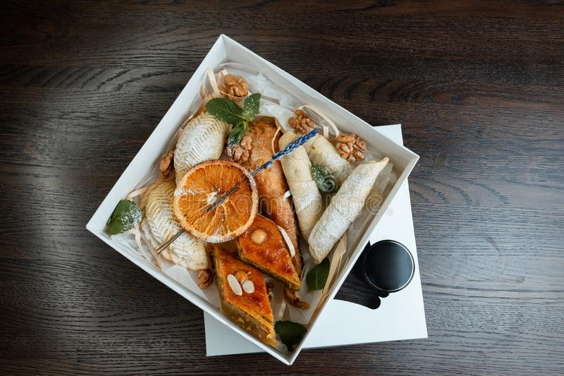 Prezenta pudełko z orientalnymi tradycyjnymi mąka cukierkami dekoruje z pomarańczowymi plasterkami i świeżymi nowymi liśćmi Wielk obrazy royalty free