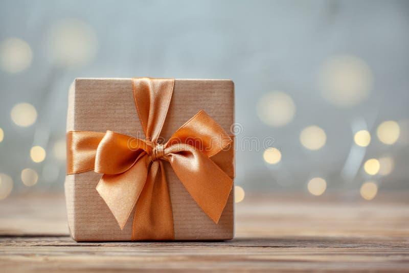 Prezenta pudełko zawijający z rzemiosło łękiem na neutralnym tle z boke i papierem fotografia royalty free