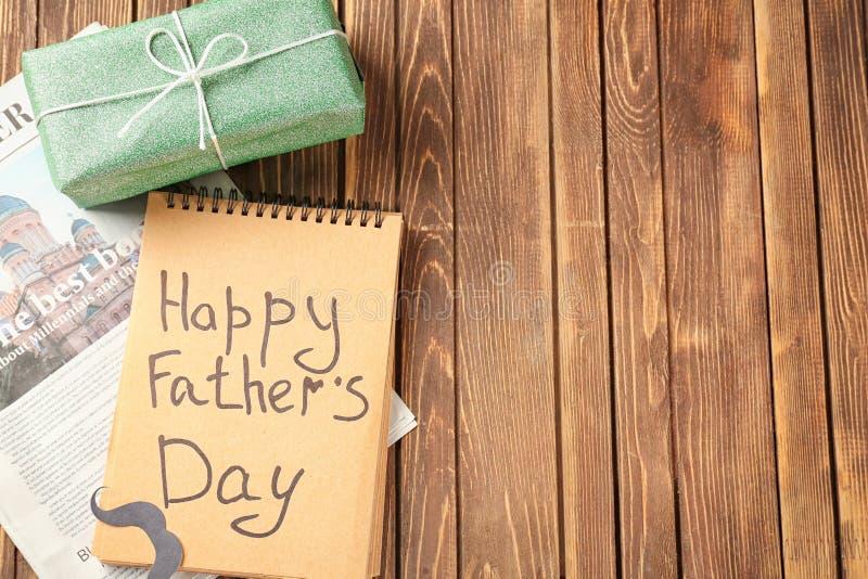 Prezenta pudełko, gazeta i notatnik z SZCZĘŚLIWĄ ojca dnia inskrypcją na drewnianym tle, fotografia royalty free