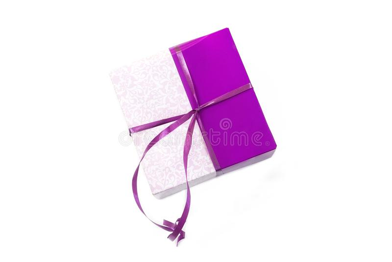 Prezenta pudełko, pakuneczek w opakunkowym papierze wiążącym z purpurami barwi faborek, pakuje egzamin próbnego up na bielu obrazy stock