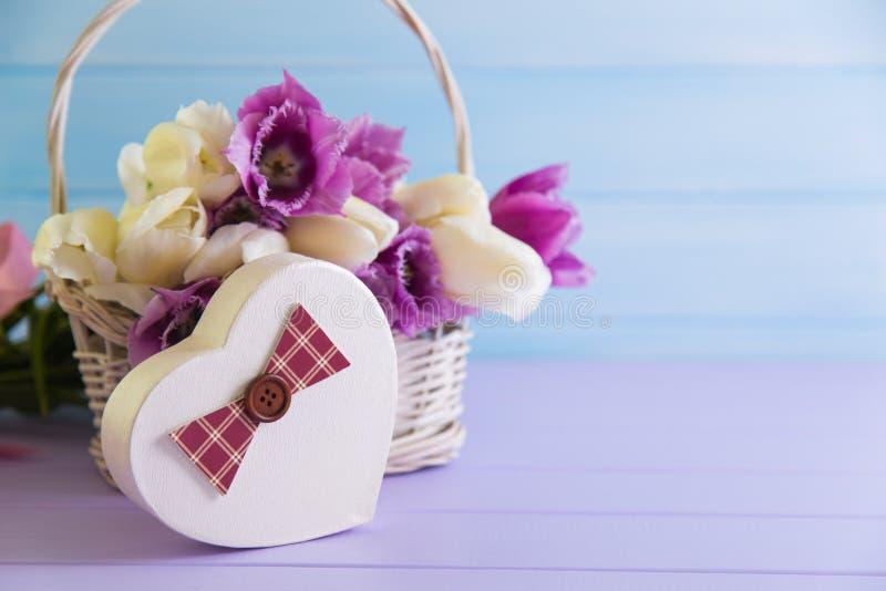 Prezenta pudełko w formie serce z koszykowy pełnym purpurowi i biali tulipany na czułym drewnianym tle obraz stock