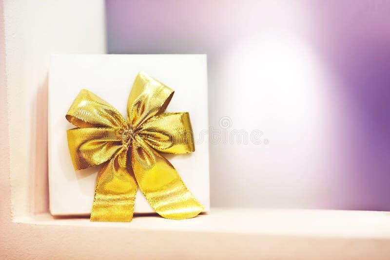 Prezenta pudełko z żółtym łękiem na purpurowym tle obraz stock