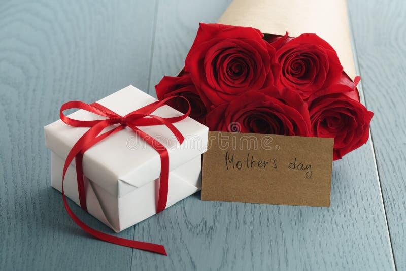 Prezenta pudełko z czerwonych róż bukietem i matka dnia papierowa karta na błękitnym drewno stole zdjęcie royalty free