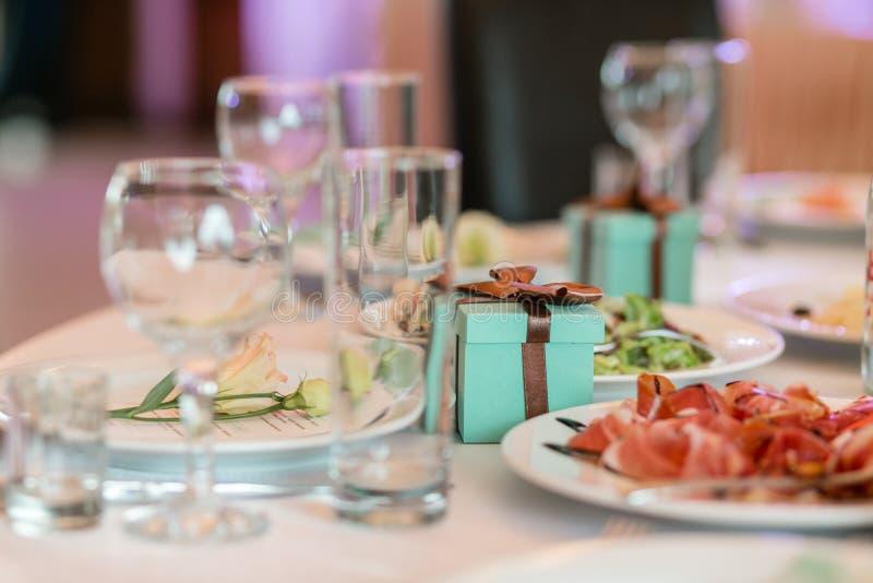 Prezenta pudełko z faborkami r elegancki wystrój i gajenie Restauracja stół z jedzeniem obrazy stock