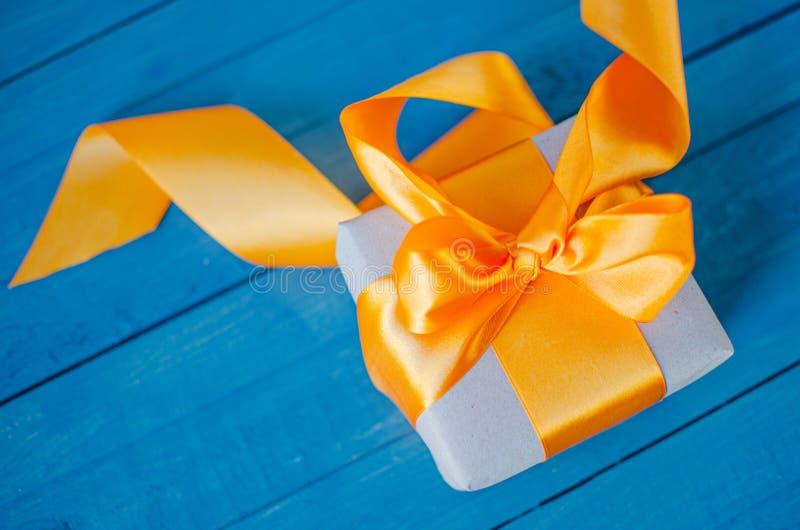 Prezenta pudełko z pomarańczowym łękiem na błękitnym drewnianym tle obrazy royalty free