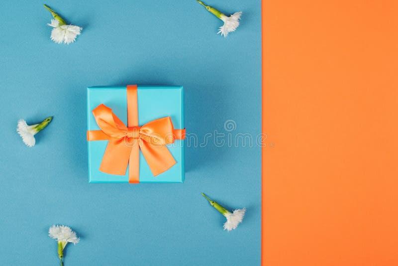 Prezenta pudełko z pomarańczowym łękiem na błękitnym tle z kwiatami, kopii przestrzeń Mieszkanie nieatutowy Odgórny widok Minimal obrazy royalty free