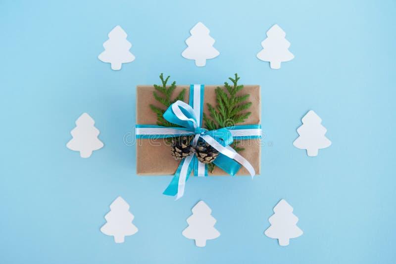 Prezenta pudełko zawijający rzemiosło papier, faborki, dekorujący jedlinowi pinecones na błękitnym tle i gałąź, błękitni i biali  obrazy royalty free