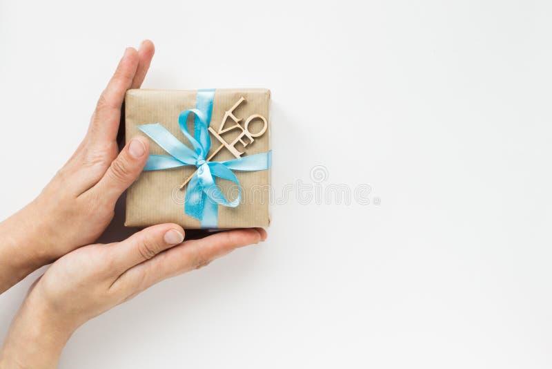Prezenta pudełko zawijający w brązu papierze z błękitnym faborkiem w kobiet rękach na białym tle Odg?rny widok Copyspace obrazy royalty free