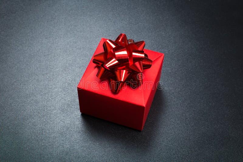 Prezenta pudełko zawijający w papierze z czerwonym faborkiem na czerni powierzchni Odg?rny widok z kopii przestrzeni? obraz royalty free