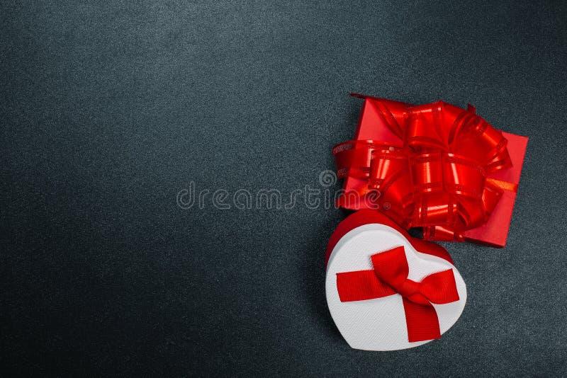 Prezenta pudełko zawijający w papierze z czerwonym faborkiem na czerni powierzchni Odg?rny widok z kopii przestrzeni? zdjęcie royalty free