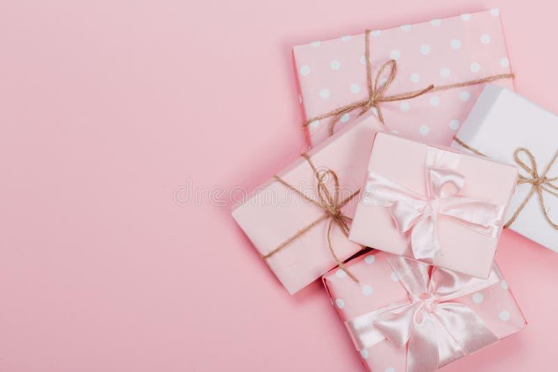 Prezenta pudełko zawijający w pastelu papierze z różowym faborkiem na menchiach ukazuje się Odgórny widok z kopii przestrzenią i obraz stock