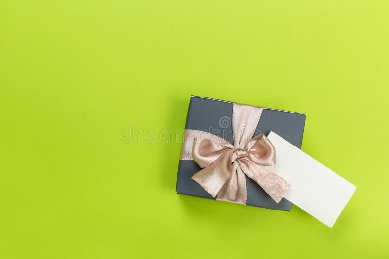 Prezenta pudełko zawijający w pastelu papierze z różowym faborkiem na zieleni powierzchni fotografia stock